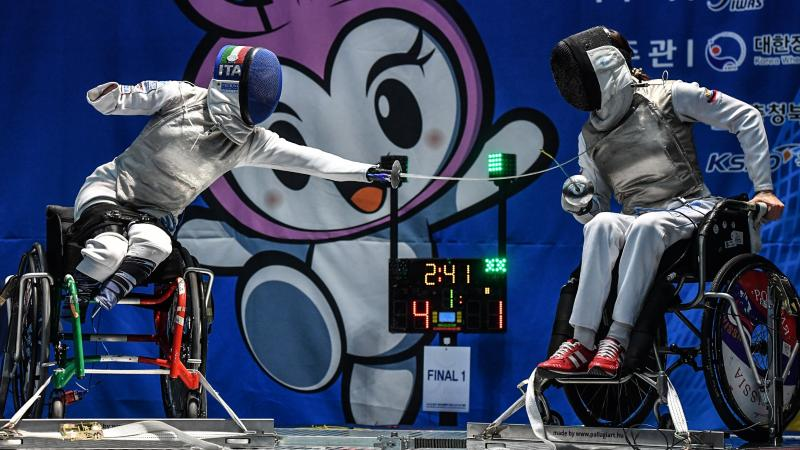 A wheelchair fencer lands a blow on her opponent