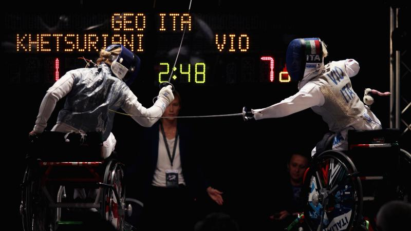 Two women in wheelchairs fencing