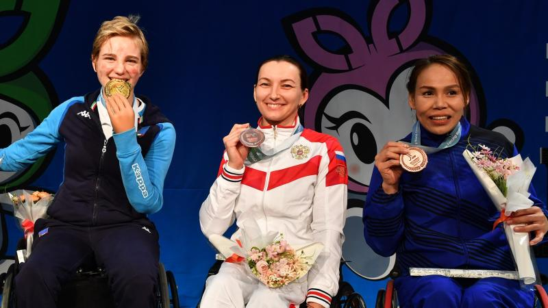 Four women pose on the podium holding their medals