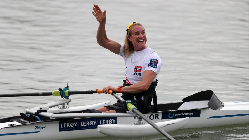 Woman in rowing boat waves at spectators