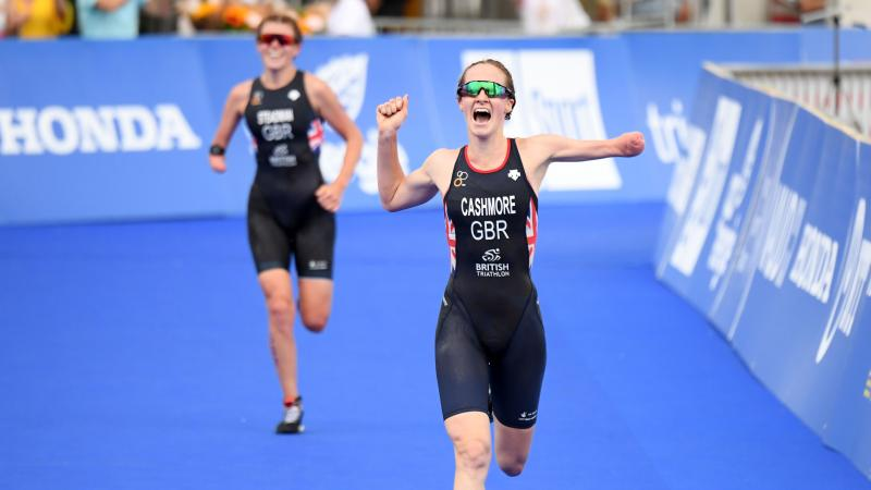 Female triathlete with arm amputation celebrates with opponent in background smiling