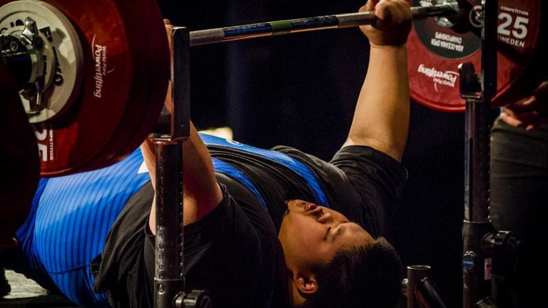 A male powerlifter lifting the bar