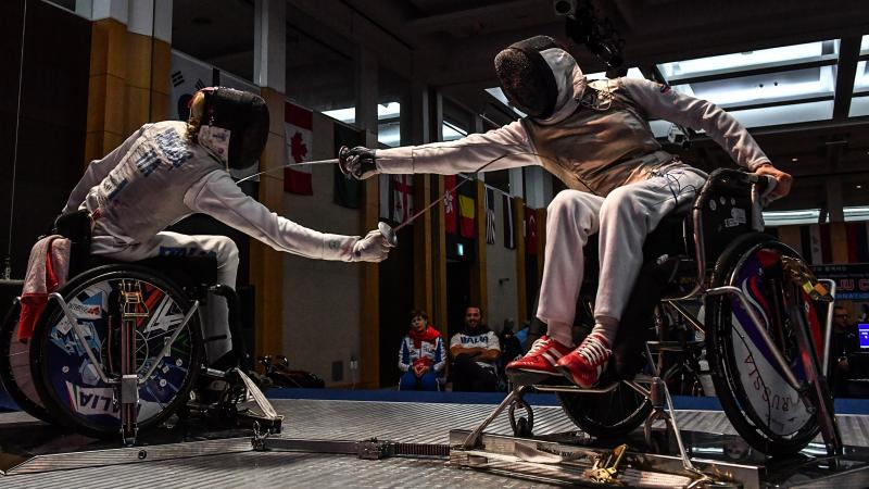 Two wheelchair fencers reach to strike their opponent
