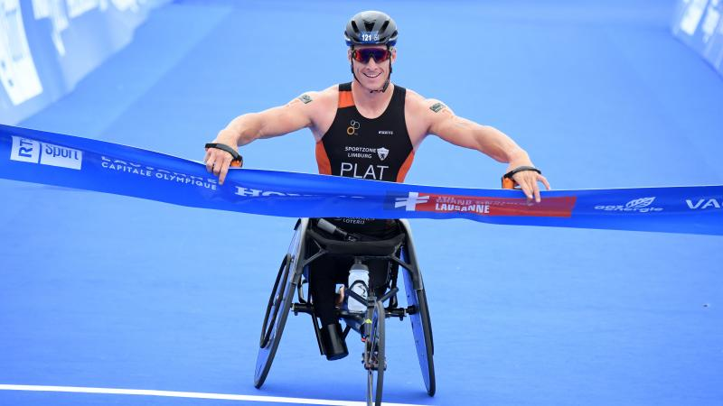 Man in racing chair smiles crossing finish line tape