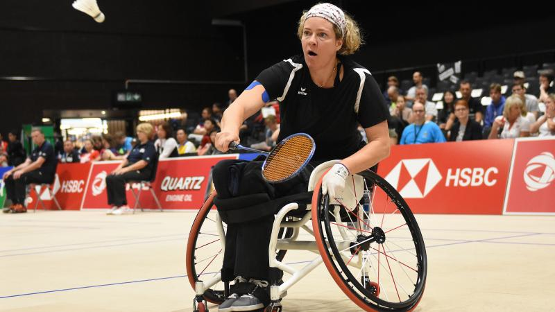 A woman in a wheelchair playing badminton
