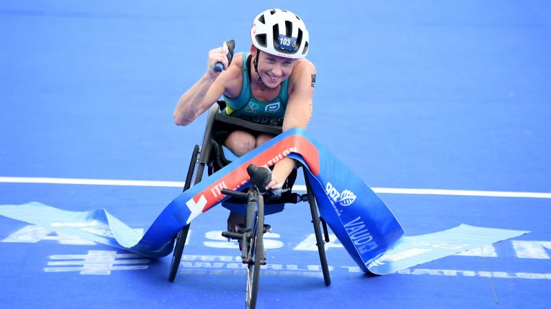 Woman in racing chair crosses finish line tape