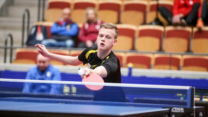 Teenage male table tennis player returns ball