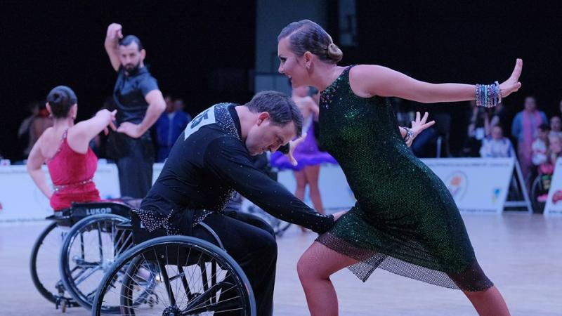 Man in wheelchair dancing with standing partner