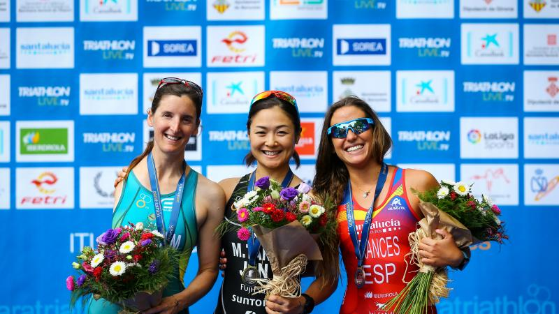 Three female Para triathletes pose together on the podium
