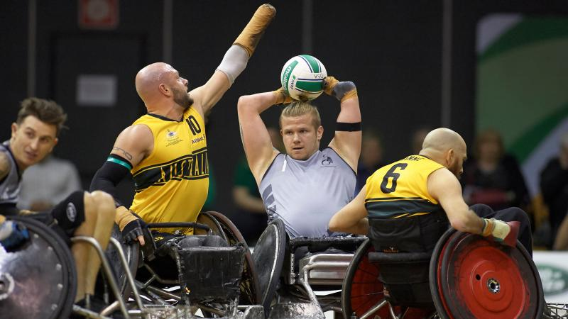New Zealand male wheelchair rugby player holds ball over head while Australian defenders try surround him