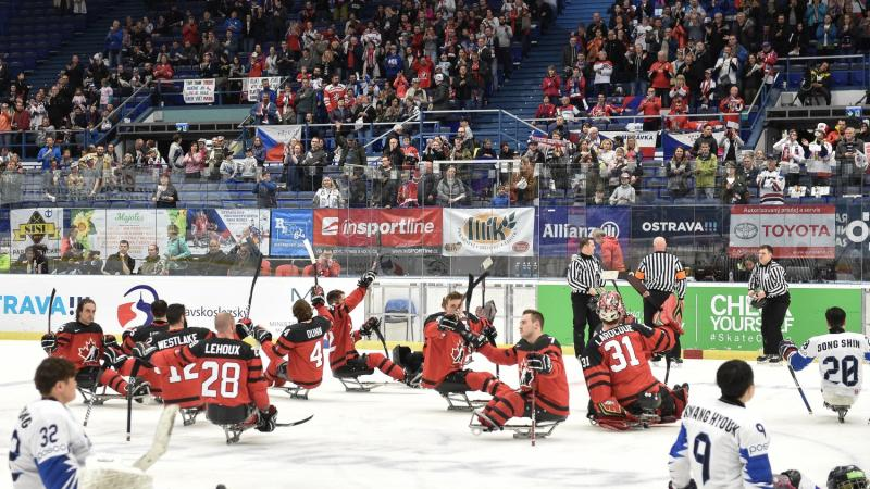 Canada hockey team celebrates on ice while South Korean team looks on