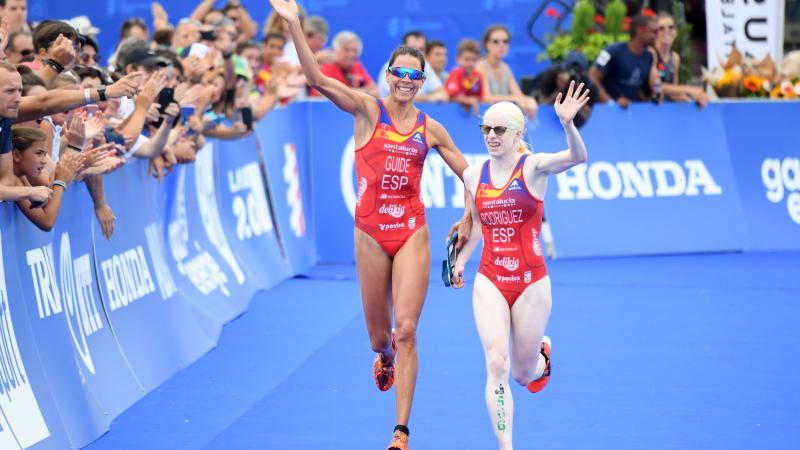 Female triathlete and her guide celebrate before crossing the finish line