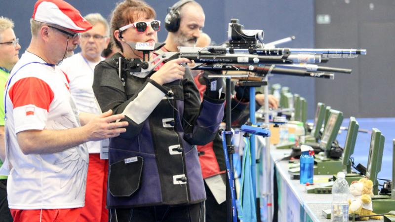 Female vision impaired rifle shooting athlete receives guidance from loader