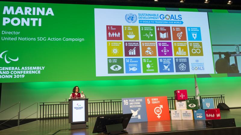 A woman on a stage making a presentation about the UN SDGs
