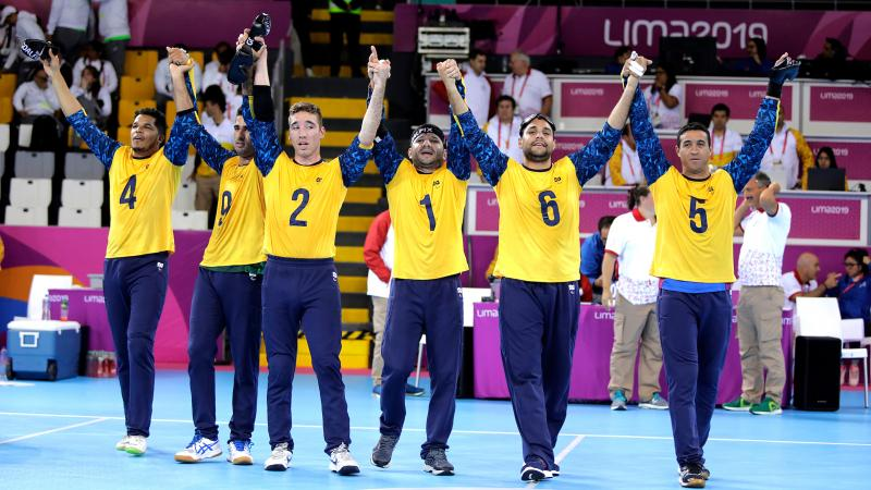 Brazilian goalball players lifting their arms to celebrate after winning the Lima 2019 competition