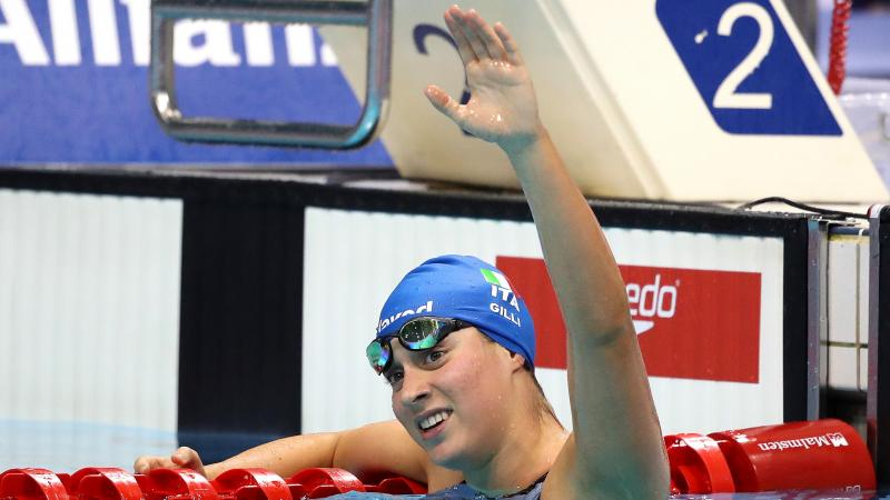 A female swimmer in the swimming pool waving