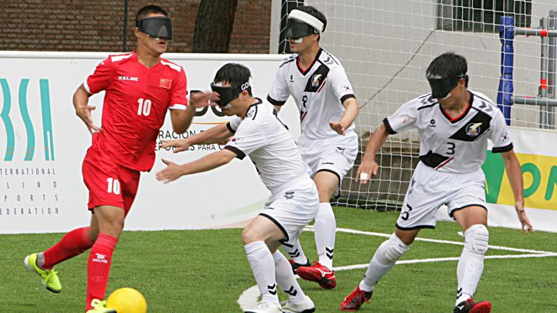 blind football player taking the ball while defenders try to intercept him