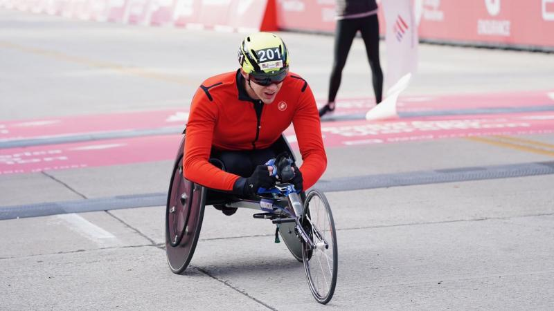 A man in a wheelchair race crossing the finish line of the Chicago Marathon