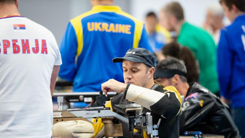 A man loading his rifle during a shooting competition with other competitors and a man standing next to him