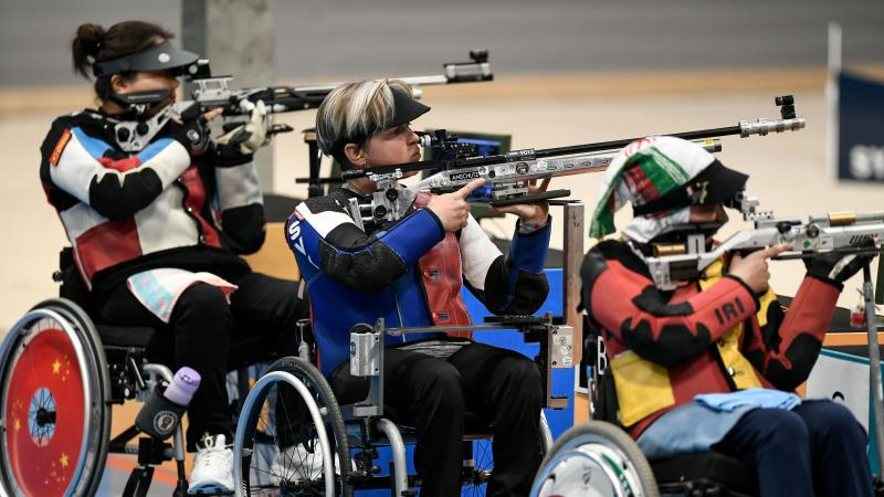 Three female shooters in wheelchairs competing with rifles