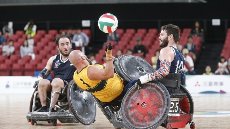 Two wheelchair rugby players knock over an opponent