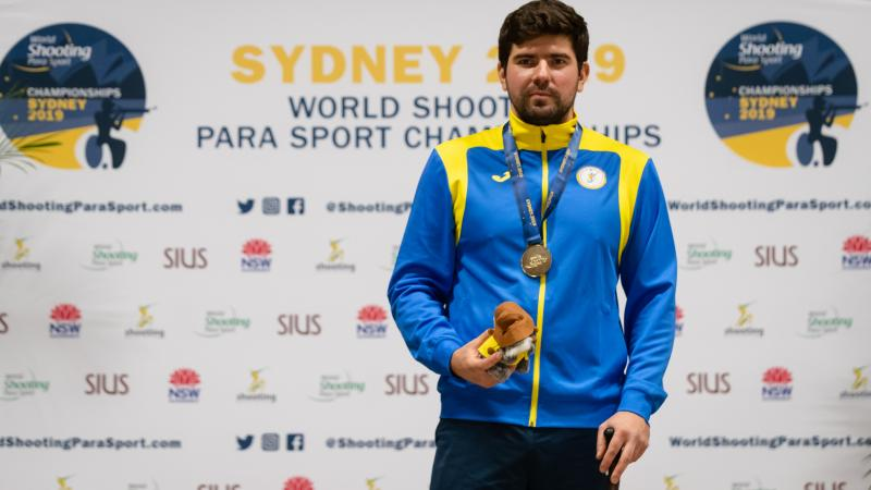 Ukrainian man stands with gold medal around neck and prize in hand