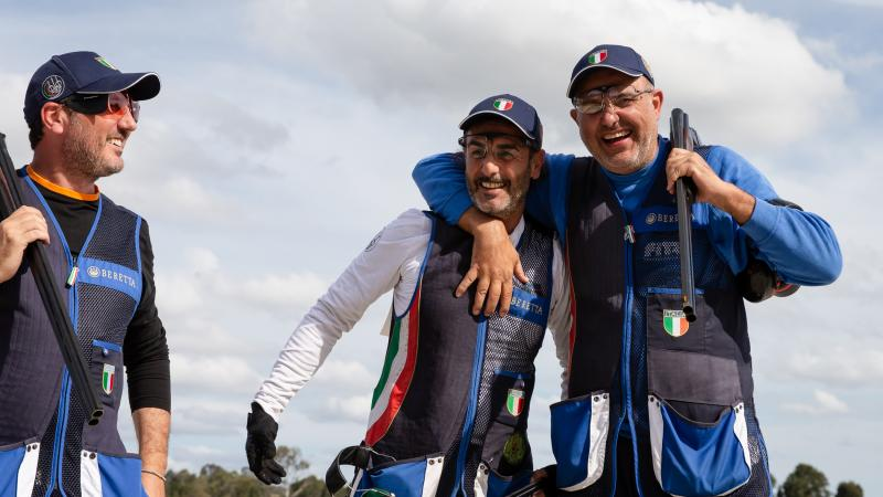 Two Italian shotgun athletes have arms around each other laughing