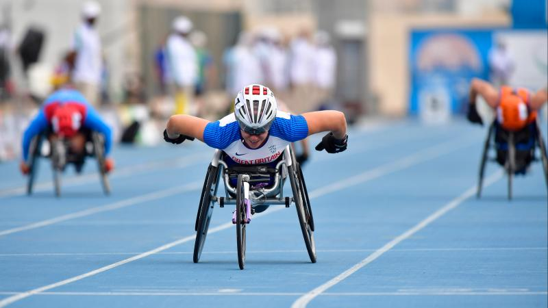 A female wheelchair racer crossing the line ahead of two other competitors
