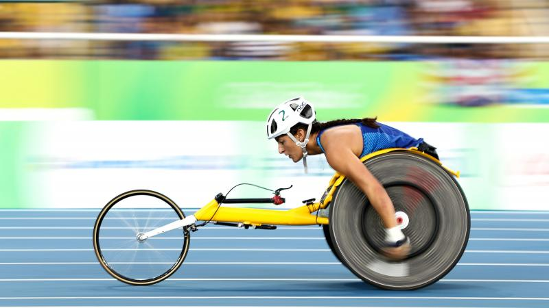 A female wheelchair racer on a blue track