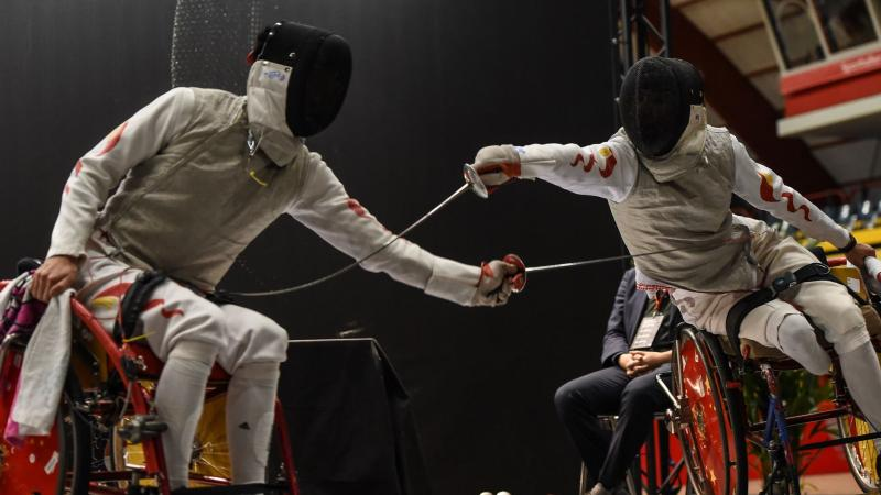 Two male Chinese wheelchair fencers battling on the piste