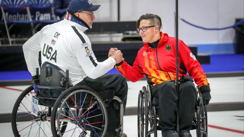 Two wheelchair curlers shake hands