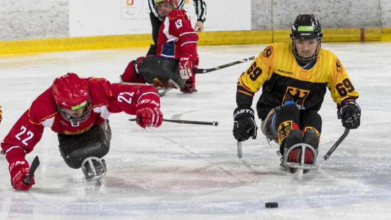Two ice hockey players go for the puck