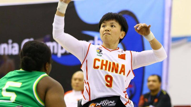 Chinese woman in wheelchair about to shoot basketball