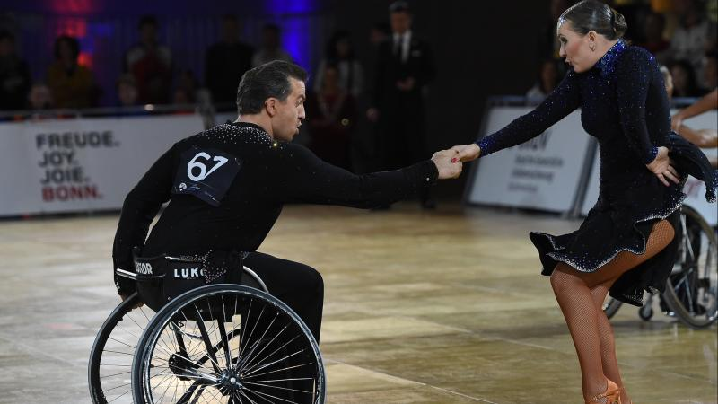 Man in wheelchair dances Latin with standing female partner