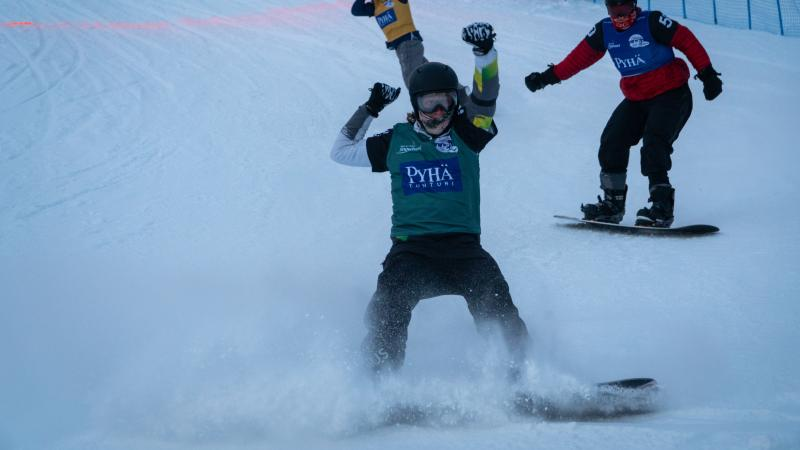 Male snowboarder celebrates after crossing finishline