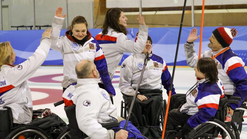 Group of Czech Republic wheelchair curlers high five each other