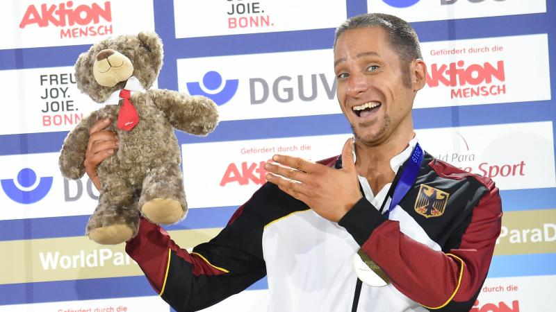 German dancer in wheelchair smiles with teddy bear prize