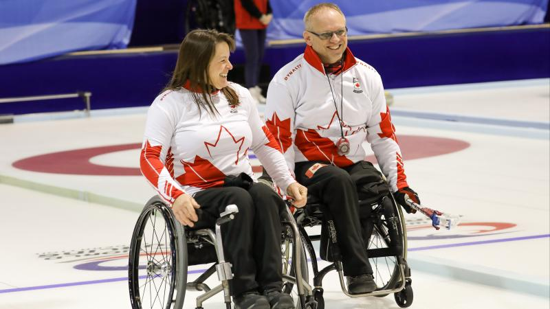 Man and woman in wheelchairs smile on curling ice sheet