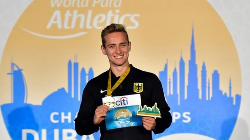 Man smiles on podium holding gold medal and prize