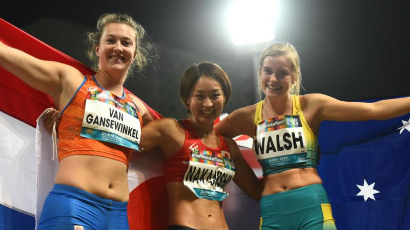 Three female longer jumpers pose for a photo with their respective flags