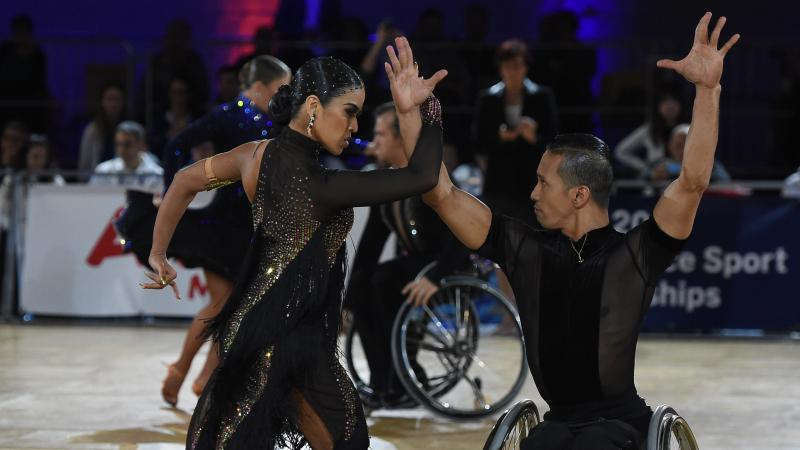 Female standing dance and wheelchair partner perform in the combi Latin 2