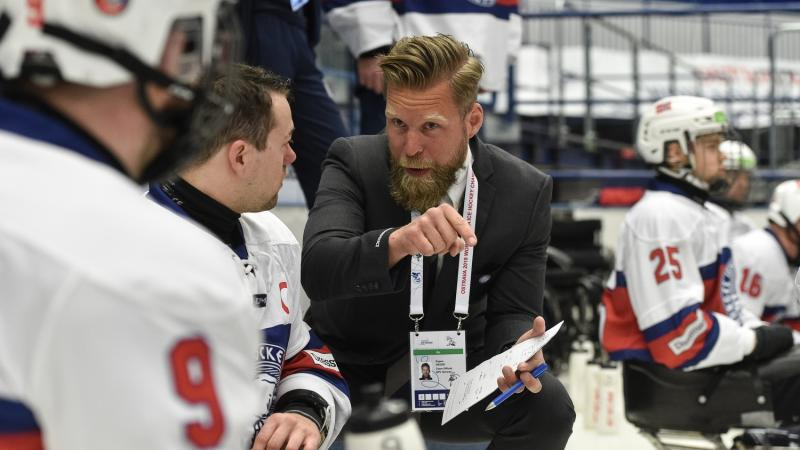 A man in suit talking to a Para ice hockey player on the ice