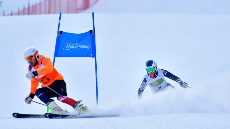 A female Para alpine skier behind her guide