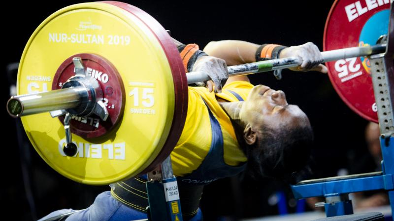 Female powerlifter holds onto the bar preparing for her lift
