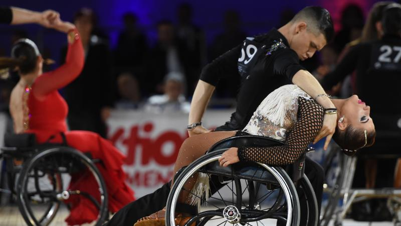 Standing male dancer dips his female wheelchair dancer