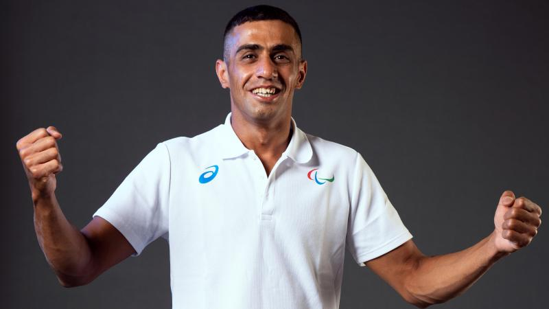 A man smiling to camera wearing a white shirt with the Agitos