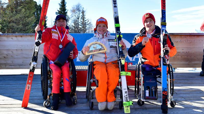 Three male sit skiers pose on the podium