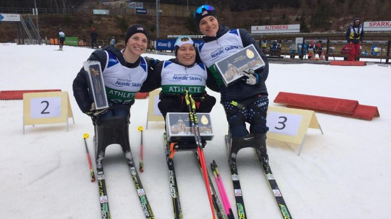 Three female sit-skiers posing with their trophies