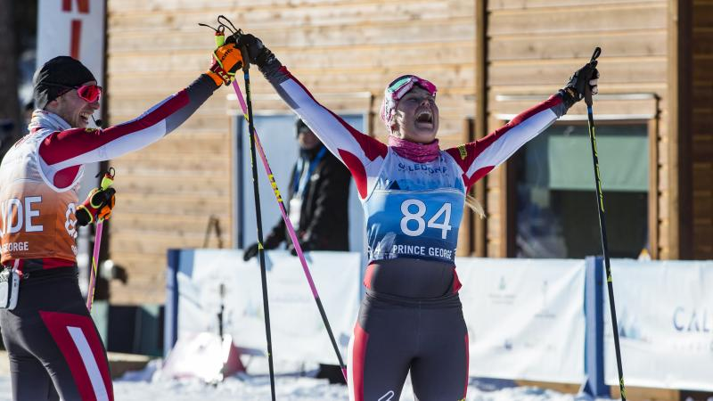 Cross-country skier lifts arms with joy with her guide on the side
