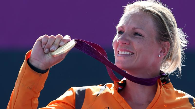 Dutch wheelchair tennis player smiles holding her gold medal at the London 2012 Paralympics